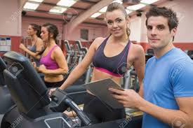 gym instructor gym instructor and woman in the gym on the treadmill stock photo