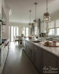 white and gray kitchen features a long gray wash oak center island topped with gray and white marble illuminated by a stainless steel sink and gooseneck