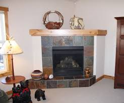 corner fireplace design ideas with slate tile and wood shelf