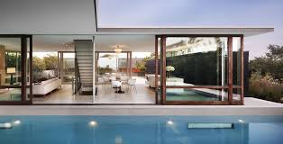 retractable clear glass wall presenting livind and dining also wooden frame slinding glass door
