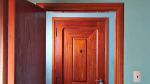 Stained interior door against blue-painted wall.