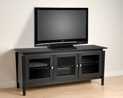 furniture black wooden tv cabinet with three doors on beige floor connected by white wall