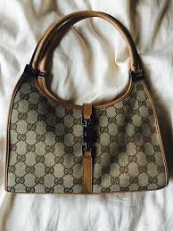 gucci vintage bags. vintage gucci monogram bag for sale. in good condition, small scratches at the bottom of bag. leather trim, plain interior with a zip pocket. bags e
