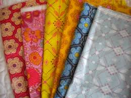 The Best Fabrics for Quilting: From Cotton to Linen & Row of Brightly Patterned Fabric Adamdwight.com
