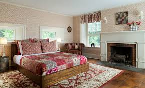 spacious cozy room with warm wood floors several windows red fl quilted bed