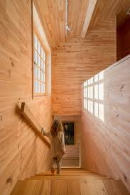 the wooden staircase of tarusa house features a large street facing window wood covers