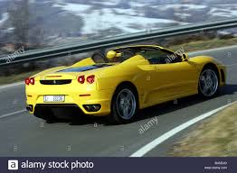 f430 ferrari yellow. car, ferrari f430 spider, model year 2005-, yellow, convertible, driving, diagonal from the back, rear view, open top, country r yellow