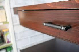 closeup of a floating pantry closet shelf with a pull out drawer underneath stained with natural