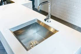 Detail Of A Rectangular Designer Kitchen Sink With Chrome Water