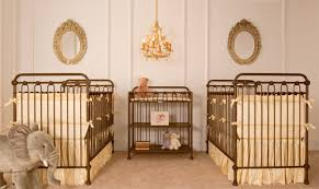 upscale baby furniture. paired gold iron cribs dressed in warm yellow makes this upscale twin nursery stylish and graceful baby furniture