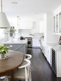 white kitchen with gray island and dark oak wood floors
