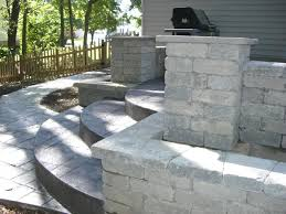 column planter and retaining wall with stamped concrete steps and raised patio