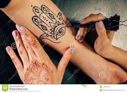 художник прикладывая татуировку Mehndi хны на женской руке стоковое