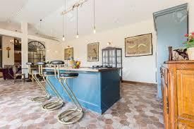 Modernes Interieur Mit Holzmöbeln, Kücheninsel Mit Stühlen In Der Mitte Und  Minimalistische Beleuchtung Standard
