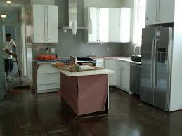 off white cabinets dark floors. black electric range under cabinet rectangle wooden island granite contertop l shaped cabinets dark wood floors with white off