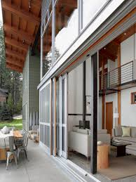 sliding exterior full glass doors for large modern house design with high ceiling and patio with exposed conrete floor tiles and outdoor dining area