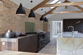 exposed original stonework of contemporary kitchen inside an old barn turned into modern home design