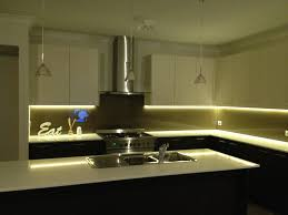 under cabinet led strip lighting and brushed nickel pendant lamp with clear glass shade above kitchen island