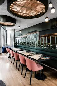 UNTIED by Techn Architecture + Interior Design. Restaurant, pink velvet  chairs, dark table, huge flush ceiling lights and wood flooring