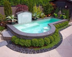 backyards design. Unique Shaped Swimming Pool Design For Small Backyards With Elegant Waterfalls And Decorative Round Shrubs I