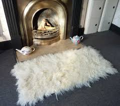 fireplace and fireplace hearth with mongolian sheepskin throw also carpet flooring for living room