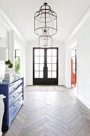 beautiful entryway featuring double front doors hanging light fixtures and chevron flooring redo home