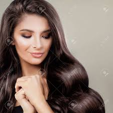 健康的なパーマをかけ髪と完璧な女性ウェーブのかかった髪型を笑顔で美しいファッション モデル