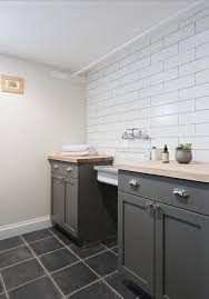 charcoal gray laundry room cabinets with wood countertops