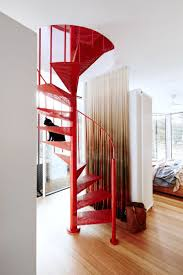A red spiral staircase punctuates the hallway and leads up to the home  office of this sustainably renovated Victorian weatherboard home in inner- Melbourne.
