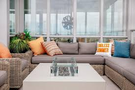 Wicker Sectional with Gray Cushions and Orange Pillows