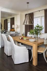chic dining room features a crate barrel big sur natural dining table lined with slipcovered