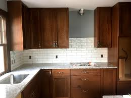 white subway tile backsplash and light colored quartz countertops contrast the darker stained cabinets