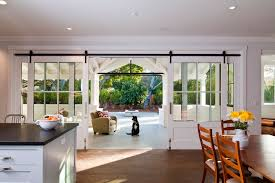 indoor barn doors with farmhouse kitchen and back porch barn door black countertop dining table farm house island muntins recessed lights sliding door white