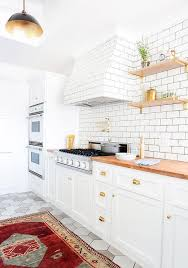 white kitchen cabinets with brass cup pulls and butcher block countertops