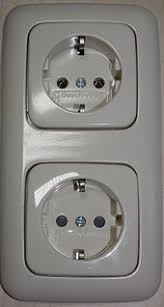 ac power plugs and sockets two schuko cee 7 3 socket outlets manufactured by busch jaeger elektro gmbh the lower has black protective shutters the upper does not