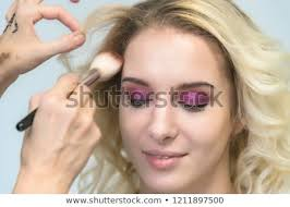 the work of a professional makeup artist beautician makes makeup with a brush on