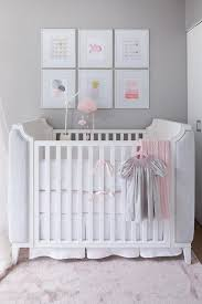 white and gray nursery crib with pink cloud mobile