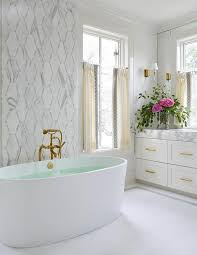 a mosaic marble accent wall stands behind an antique brass vintage bathtub filler and an oval freestanding bathtub flanked by windows