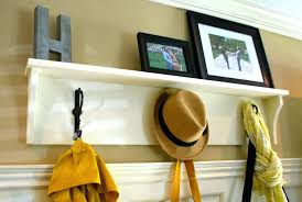 wall coat rack ideas white wooden shelf with three hangers on the interior  connected by racks