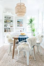 Beachy dining space with an IKEA pendant light, white metal chairs, and  lamb throws for an eclectic boho dining room idea.
