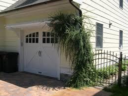 jasmine vine on eyebrow pergola above a garage door