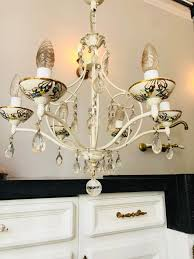 a beautiful chandelier with porcelain bowls and crystal pendants and painted with yellow and blue flowers