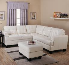 l shaped white leather loveseat and ottoman coffee table with black wooden base on