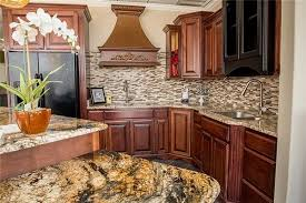 kitchen island with golden crystal granite paired with stone radiance tile backsplash ornamental granite countertops and saddle brown cabinets