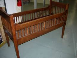 antique brown stained wooden baby nursery bed with vintage baby crib on wheels and