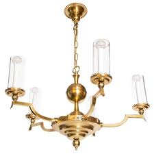 scandinavian modern five arm brass chandelier with cylindrical glass shades for