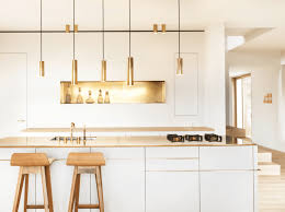 white wooden kitchen island gold pendant light gold faucet