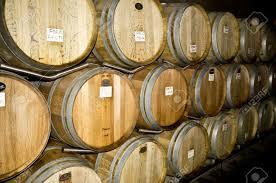 oak wine barrels. rows of oak wine barrels aging in a chilled cellar at california winery stock