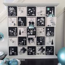 wooden advent calendar painted black and white and decorated with silver numbers black and white