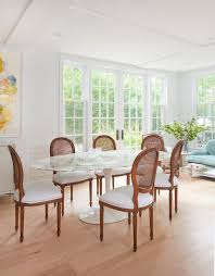 chic sp dining room boasts an oval marble top dining table saarinen oval dining table surrounded by french cane dining chairs with upholstered white